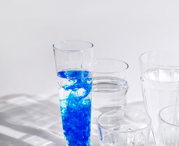 Blue ink dissolved in water inside the glass against white background