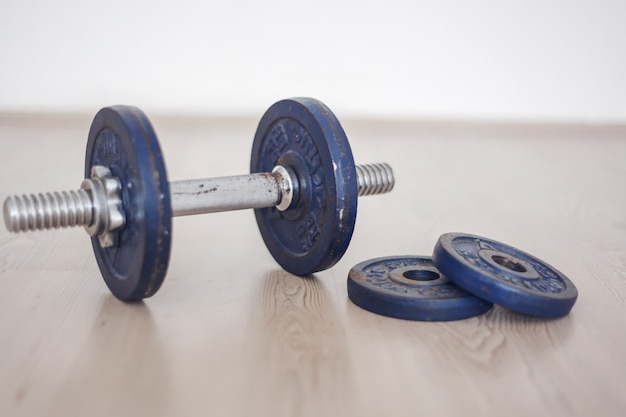 Blue iron dumbbell on the floor. lifting weight. workingout at home concept.