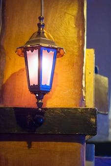 Blue iron lantern on the yellow wall