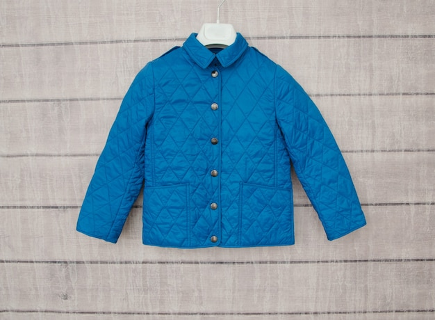 Синий пиджак висит на вешалке