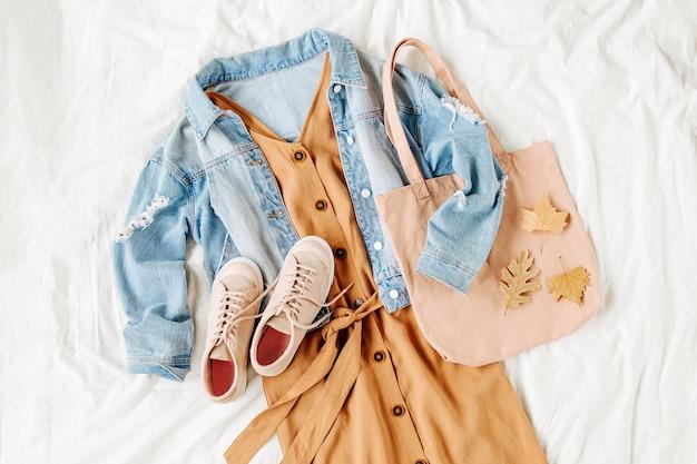 ブルージーンズのジャケットとベージュのドレス、白いベッドにトートバッグが付いたスニーカー。女性のスタイリッシュな秋の服。流行りの服。フラットレイ、上面図。