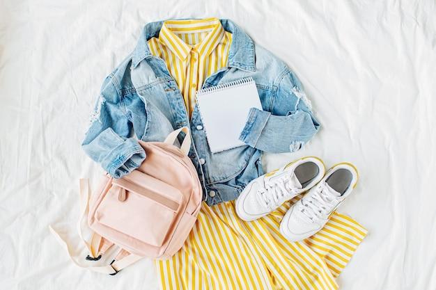 Синяя джинсовая куртка и желтое платье с рюкзаком, книгой и кроссовками на белом. стильный женский осенний или весенний наряд. модная одежда для колледжа. снова в школу концепции. плоская планировка, вид сверху.
