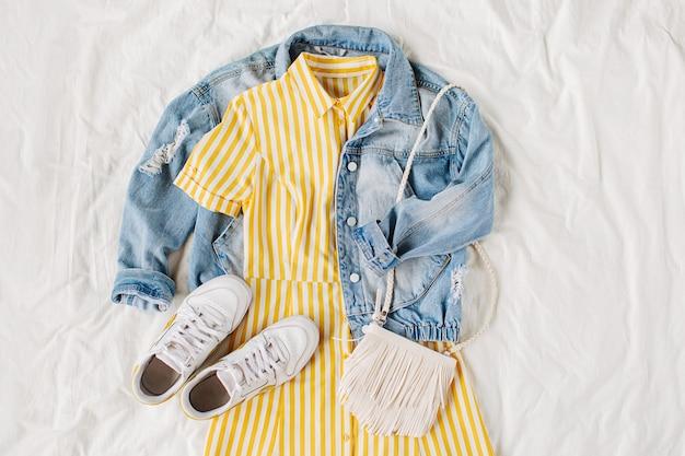 ブルージーンズのジャケットと黄色のドレス、白いベッドにバッグとスニーカー。女性のスタイリッシュな秋または春の衣装。流行りの服。ファッションコンセプト。フラットレイ、上面図。