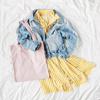 흰색 침대에 에코백이 달린 청바지 재킷과 노란색 드레스. 여성의 세련된 가을 또는 봄 복장. 에코백 모형이 있는 트렌디한 옷. 패션 개념입니다. 평평한 평지, 평면도.