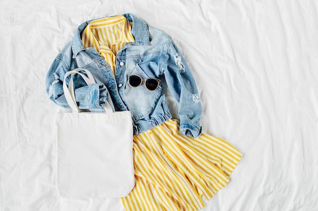 Синяя джинсовая куртка и желтое платье с эко-сумкой на белой кровати. стильный женский осенний или весенний наряд. модная одежда с макетом белой эко-сумки. концепция моды. плоская планировка, вид сверху.