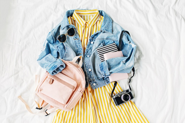 Blue jean jacket and yellow dress  with backpack, book and photo camera on white. women's stylish autumn or spring outfit. trendy clothes for college. back to school concept.  flat lay, top view.