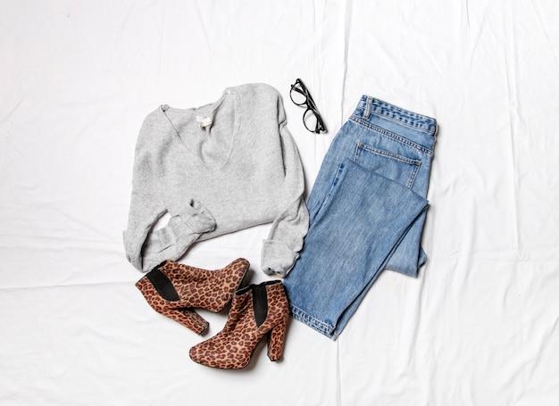 ブルージーンズ白いシートにニットセーターカジュアルな女性の日の服の上面図