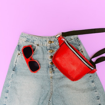 ブルージーンズとファッションレッドのアクセサリー。クラッチバッグとサングラス
