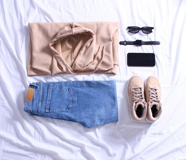 ブルージーンズ、ベージュのスウェットシャツ、ベージュのスニーカー、黒のサングラス、携帯電話、ベッドの上の白いシートに腕時計。