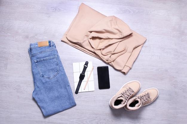 ブルージーンズ、ベージュスウェットシャツ、ベージュスニーカー、ノートブック、携帯電話、腕時計