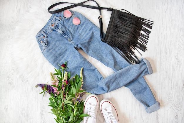 ブルー ジーンズ、黒のハンドバッグ、白のスニーカー、花。白色の背景。ファッショナブルなコンセプト