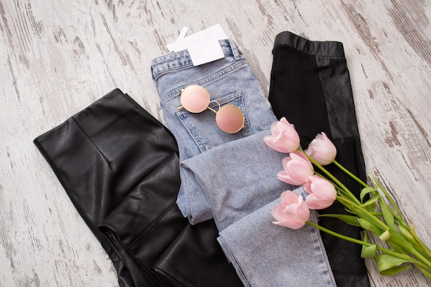 Blue jeans and black leather leggings, glasses, pink tulips.