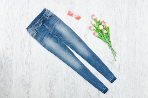 Blue jeans and bouquet of tulips. fashionable concept