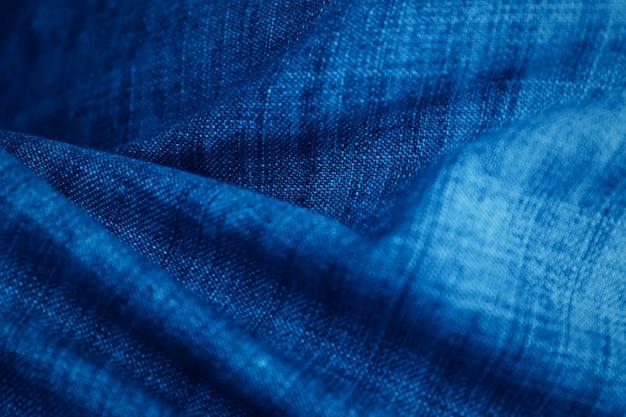 ブルージーンズは、テクスチャの背景を閉じます。ジーンズの背景、水色のナチュラルクリーンデニムの質感。クリエイティブな色合い。トレンドカラークラシックブルー。 2020年の色。