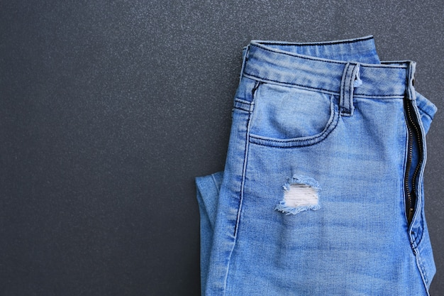 Синие джинсы складываются на темном фоне плитки. джинсовая одежда с копией пространства