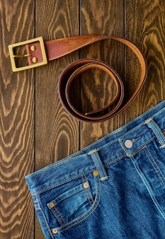 Blue jeans and leather belt on wooden table