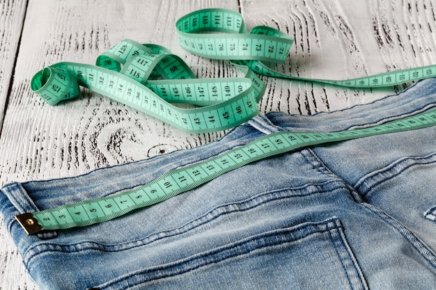 Blue jeans and measuring tape in waistband and in body