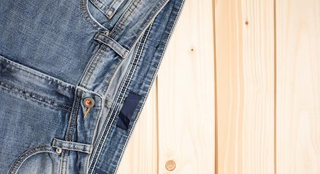 デニムの木製の背景のテクスチャにブルージーンズ上面図