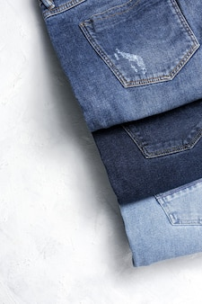 ブルージーンズパンツ服パイル背景。素敵なブルージーンズのディテール