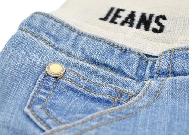Маленький карман синих джинсов с желтой пуговицей и растягивающимся поясом.