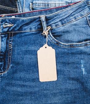 Синие джинсы с коричневой бумажной пустой биркой на веревке