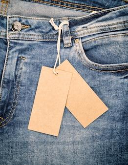 Синие джинсы с коричневой бумажной биркой на веревке