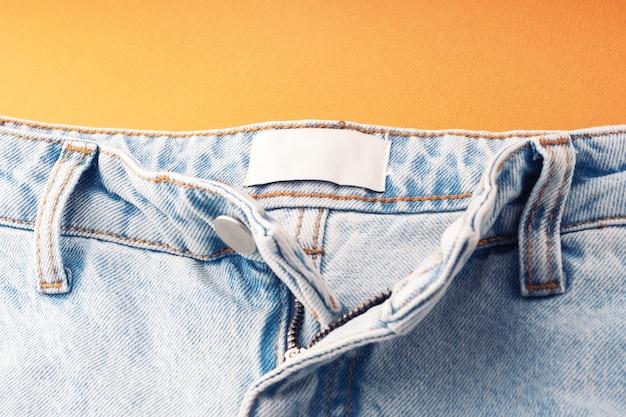 白い空白のラベルが付いたブルージーンズ、クローズアップ。ジーンズの質感。縫製、コピースペースのファッションデニムの背景。サイズ、会社を示すために衣類のラベル。