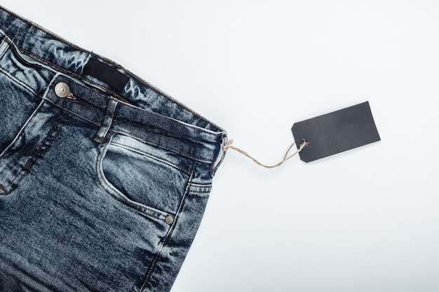 Blue jeans with a blank tag on a rope. white surface