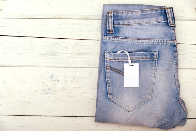 Blue jeans with blank white price label tag on shabby wooden table.