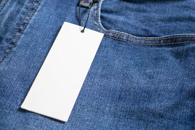 Синие джинсы с пустым белым ценником