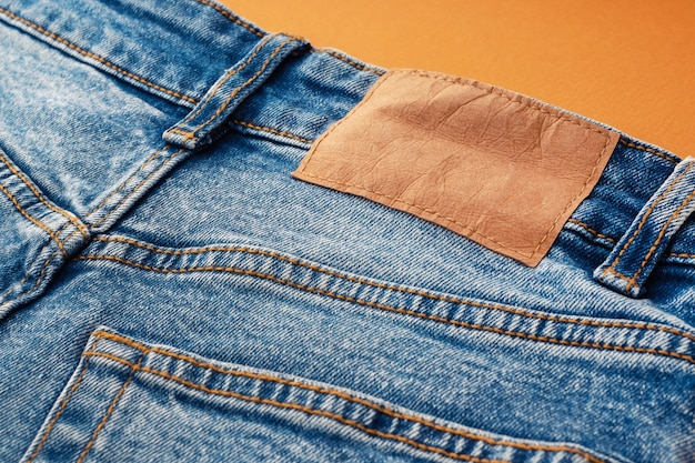 Blue jeans with a brown leather blank label, close-up. jeans texture. fashion denim background for sewing, copy space. label on clothing for indicate the size, company.