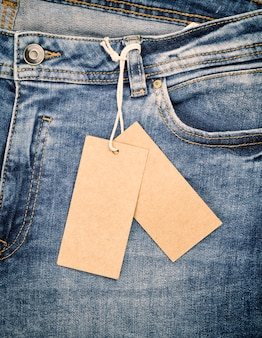 Blue jeans with a brown paper tag on a rope