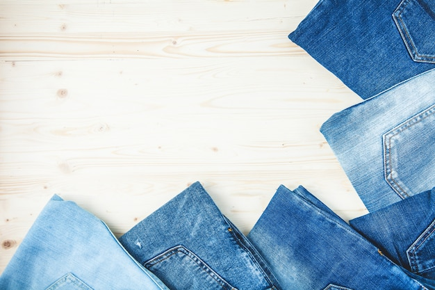 Blue jeans on a wooden background copy space top view