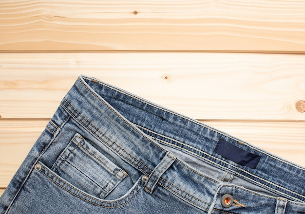 Blue jeans on a wooden background texture of denim top view