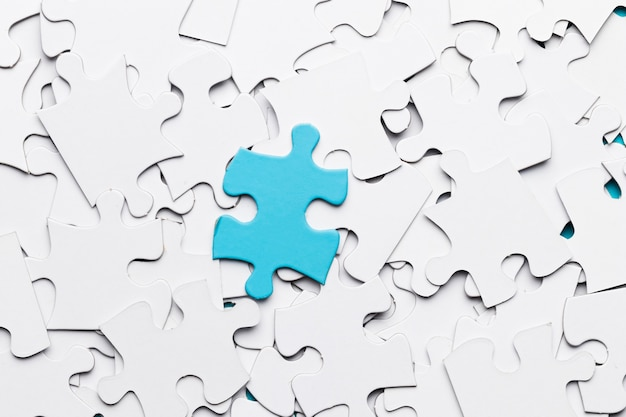 Blue jigsaw puzzle piece over white puzzle pieces