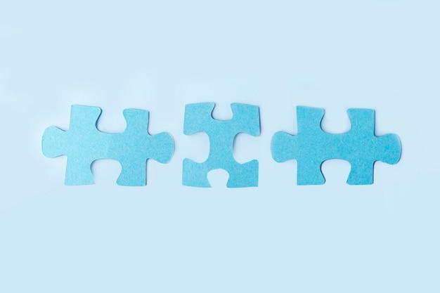 Синие кусочки головоломки на желтом фоне. логическое мышление в команде. концепция решений, миссии, успеха, целей, сотрудничества и партнерства. скопируйте место для текста.