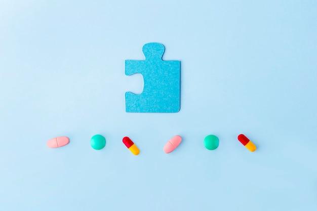 Синие кусочки головоломки с различными таблетками и лекарствами. концепция лечения неврологических заболеваний: аутизм, болезнь альцгеймера, измерение. скопируйте место для текста. день осведомленности. поддержка и принятие.