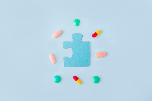 Blue jigsaw puzzle pieces with different pills and medicines. concept of neurological disease treatment : autism, alzheimer's, dimension. copy space for text. awareness day. supportive and acceptance.