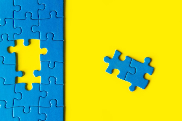 Blue jigsaw puzzle on yellow background, business connection, success and strategy concept, teamwork