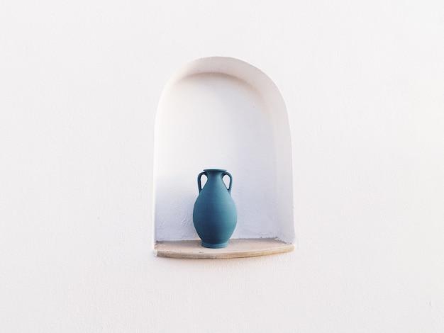 白い壁の開口部にある青い水差し-クールな背景に最適