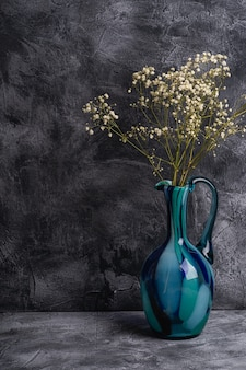 Blue jug vase with bulk gypsophila dried white flowers on dark textured stone wall, angle view