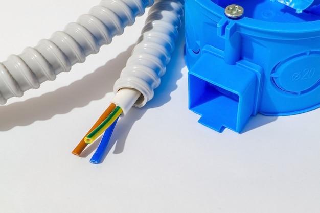 Распределительная коробка синего цвета с проводом для ремонта электрики