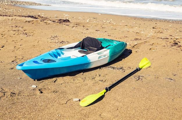 Синий каяк, лежащий на песчаном пляже