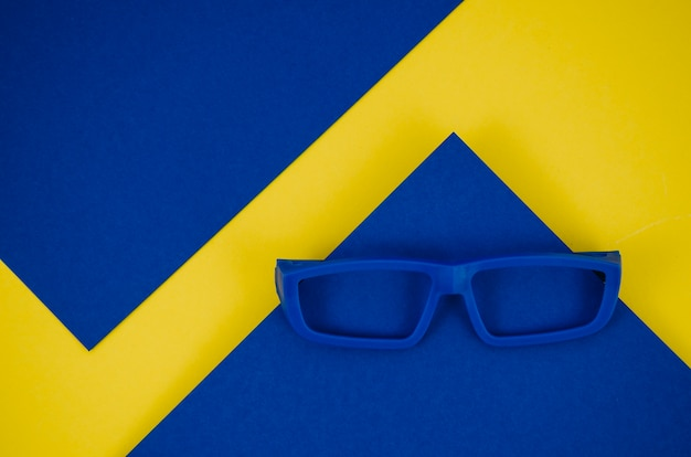 Blue kids eyeglasses on blue and yellow background