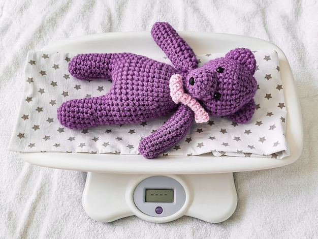 A blue knitted teddy bear lies on an electronic baby scale on a diaper with stars