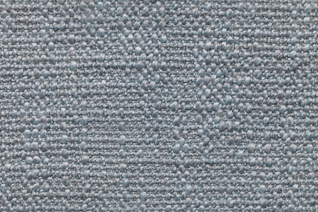 Blue knitted woolen background with a pattern of soft, fleecy cloth. texture of textile closeup.