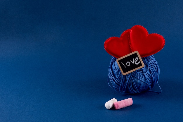 Blue knitting threads with red hearts on classic blue 2020 color background. valentines day 14 february diy concept. copy space, top view, banner.