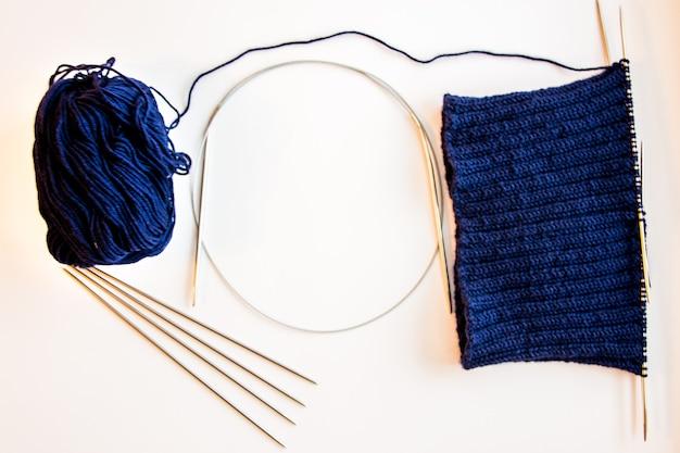 青い編みウールと編み針。編み物の帽子。