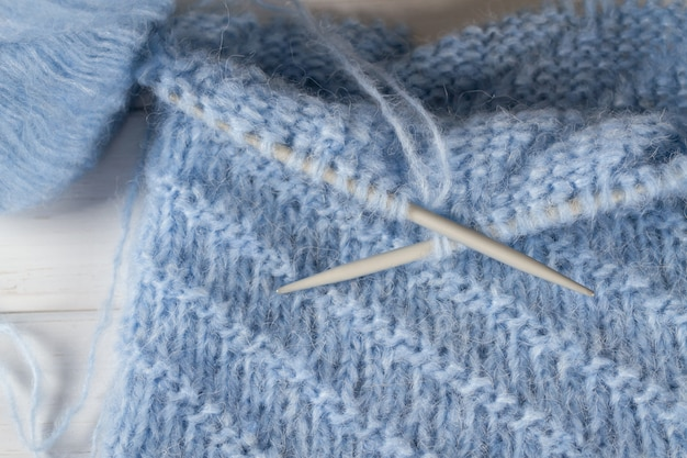 Blue knitting wool yarn and knitting needles. incomplete knitting project