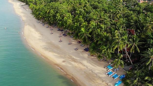 Голубая лагуна и песчаный пляж с пальмами. вид с воздуха на голубую лагуну и шезлонги на песчаном пляже с кокосовыми пальмами и бунгало на крыше.